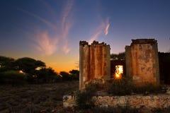 Reizender Sonnenuntergang in Kalahari mit altem Haus lizenzfreie stockfotografie