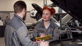 Reizender weiblicher Mechaniker, der die Kenntnisse, sprechend mit einem Kollegen an der Garage nimmt stock video