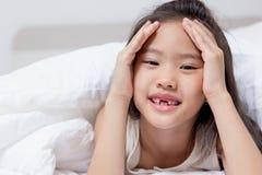 Reizendes asiatisches Kind, das auf dem Bett niederlegt Lizenzfreie Stockbilder