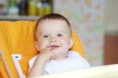 Reizendes Baby, das auf Babystuhl sitzt Lizenzfreie Stockbilder