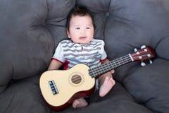 Reizendes Baby, das auf dem weichen Sofa mit Minigitarre sitzt Babymusiker Praxismusikfähigkeiten für Kinder Musik und Kinder Lizenzfreies Stockbild
