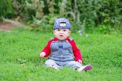 Reizendes Baby, das auf Gras im Park sitzt Stockbilder