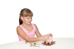 Reizendes Baby, das Geld in das Sparschwein lokalisiert einsetzt Lizenzfreies Stockbild