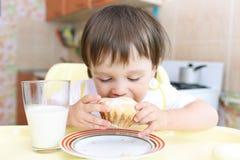 Reizendes Baby, das kleinen Kuchen und Milch isst Stockfotos