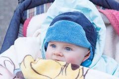 Reizendes Baby im Freien in der warmen Winterkleidung. Stockfotografie