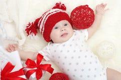 Reizendes Baby im roten Hut, der unter Geschenken liegt Stockfotografie
