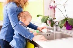 Reizendes Baby möchte seiner Mutter helfen, die Teller zu waschen lizenzfreie stockfotografie