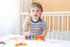 Reizendes Baby mit Bürste und Farben Stockfotos