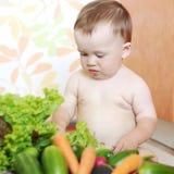Reizendes Baby mit Gemüse auf Küche Lizenzfreie Stockfotos