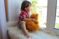 Reizendes Baby mit Plüschbären schaut aus Fenster heraus Lizenzfreies Stockfoto