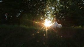 Reizendes blondes Braut- und Bräutigamtanzen im Freien im Sonnenunterganglicht, betrachtend ihrer Hochzeit glücklich stock footage
