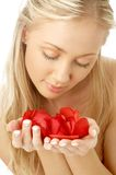 Reizendes blondes im Badekurort mit den roten rosafarbenen Blumenblättern Stockfotos