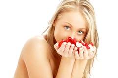 Reizendes blondes im Badekurort mit den roten und weißen rosafarbenen Blumenblättern Lizenzfreie Stockfotos