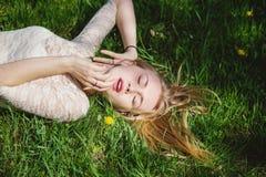 Reizendes blondes Lügen auf grünem Gras Lizenzfreie Stockfotos