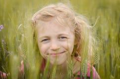 Reizendes blondes Mädchenporträt auf dem grünen Gebiet Lizenzfreie Stockfotografie