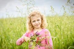 Reizendes blondes Mädchenporträt auf dem grünen Gebiet Lizenzfreies Stockfoto
