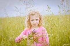 Reizendes blondes Mädchenporträt auf dem grünen Gebiet Stockbild