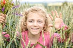 Reizendes blondes Mädchenporträt auf dem grünen Gebiet Stockfoto
