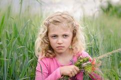 Reizendes blondes Mädchenporträt auf dem grünen Gebiet Lizenzfreie Stockfotos