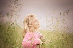 Reizendes blondes Mädchenporträt auf dem grünen Gebiet Lizenzfreies Stockbild