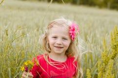 Reizendes blondes Mädchenporträt auf dem grünen Gebiet Stockfotos