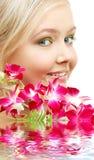 Reizendes blondes mit Orchidee im Wasser Lizenzfreies Stockfoto