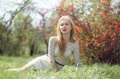 Reizendes blondes Sittting auf dem Gras unter Frühlings-Blumen-Garten Stockfoto