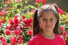 Reizendes Brunettemädchen mit dem Hintergrund von roten Rosen Lizenzfreie Stockfotos