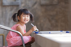 Reizendes Gesicht von den toothy lächelnden asiatischen Kindern practive zum Schreiben Lizenzfreie Stockfotos