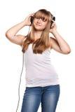 Reizendes hörendes Mädchen eine Musik in den Kopfhörern lizenzfreies stockbild