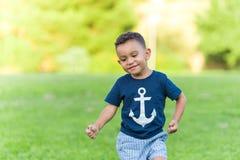 Reizendes Jungenin einem Park spielen und -betrieb draußen stockfotografie