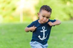 Reizendes Jungenin einem Park spielen und -betrieb draußen stockfoto