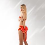 Reizendes junges blondes Fraugeschenk mit roten Bändern auf dünnem sexuellem b Stockfotos