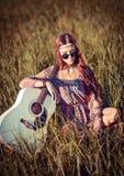 Reizendes junges Hippiemädchen mit der Gitarre, die auf Gras sitzt Stockbild