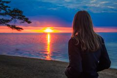 Reizendes junges Mädchen bei Sonnenuntergang in dem Meer Lizenzfreie Stockfotos