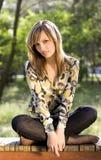 Reizendes junges Mädchen, das in einem Park sich entspannt lizenzfreies stockfoto