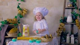 Reizendes Kind, Mädchen, das Kuchen in der Küche macht stock footage
