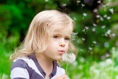 Reizendes kleines blondes kleines Mädchen, das einen Löwenzahn durchbrennt Lizenzfreies Stockbild