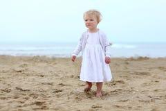 Reizendes kleines Mädchen, das auf dem Strand spielt Stockbild
