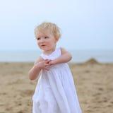 Reizendes kleines Mädchen, das auf dem Strand spielt Stockbilder