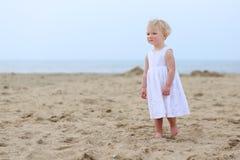 Reizendes kleines Mädchen, das auf dem Strand spielt Lizenzfreies Stockfoto