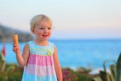 Reizendes kleines Mädchen, das Eiscreme auf dem Strand isst Stockfoto