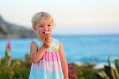 Reizendes kleines Mädchen, das Eiscreme auf dem Strand isst Stockbilder