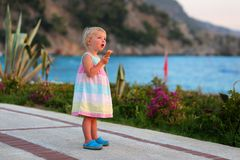 Reizendes kleines Mädchen, das Eiscreme auf dem Strand isst Stockfotos