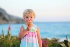 Reizendes kleines Mädchen, das Eiscreme auf dem Strand isst Lizenzfreies Stockfoto