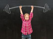 Reizendes kleines Mädchen, das herauf drawm Barbell mit zwei Händen steigt stockbild