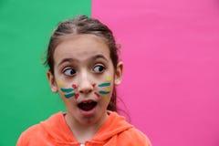 Reizendes kleines Mädchen, das lustiges Gesicht macht Stockbild