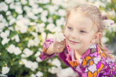 Reizendes kleines Mädchen mit einer Blume Stockfoto