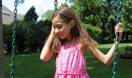 Reizendes kleines Mädchen am Schwingen im Park mit rosa Kleid während des Sommers in Michigan stockfoto