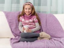 Reizendes kleines Mädchen auf einem Sofa mit warmer Decke Stockfotografie
